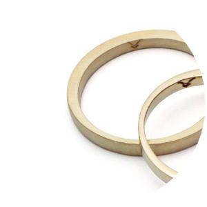 Aliança em prata ou ouro, forjada, compondo uma transição entre largura e altura do fio harmônica e bela.